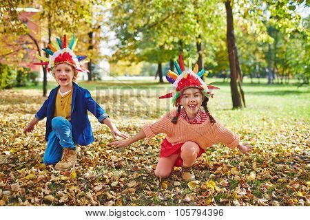 Cheerful girl and boy in Indian headdresses playing outdoors