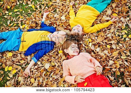 Group of little friends lying on autumn ground covered with dry leaves