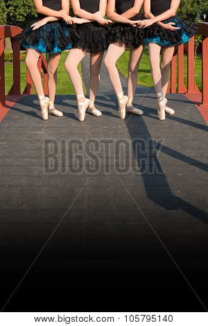 Four ballerinas hold hands in same pose
