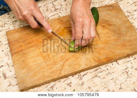 The Chef Cuts The Cucumber On A Wooden  Board.