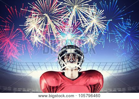 American football player holding ball while looking up against fireworks exploding over football stadium