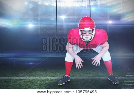 American football player in attack stance against american football arena