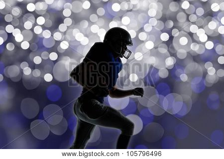 Silhouette American football player runing against glowing background