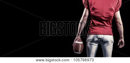 Mid section of American football player with ball against black