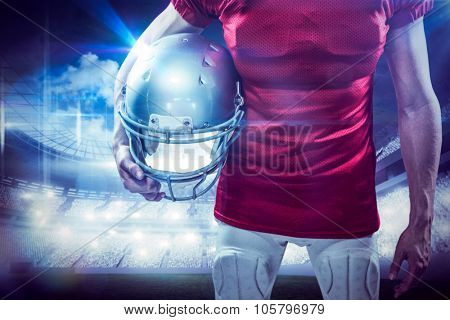 American football player holding helmet aside against sports arena