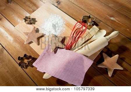 baking, cooking, christmas and food concept - close up of gingerbread cookies, molds with flour and kitchenware set on wooden cutting board at home kitchen from top