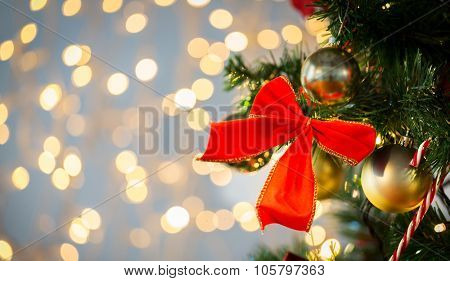 holidays, new year, decor and celebration concept - close up of christmas tree decorated with red bow and balls