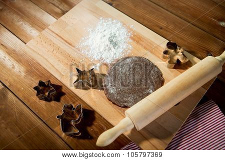 baking, cooking, christmas and food concept - close up of gingerbread dough, metal molds and rolling pin with flower on wooden cutting board at home kitchen from top