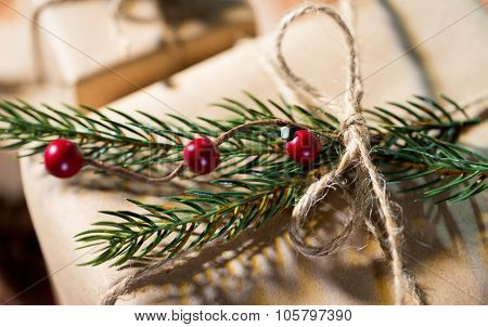 christmas, holidays, presents, new year and decor concept - close up of gift box wrapped into brown mail paper and decorated with fir brunch and rope bow