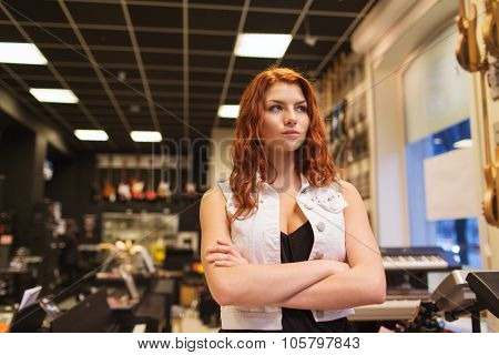 music, sale, people, musical instruments and entertainment concept - female assistant or customer at music store