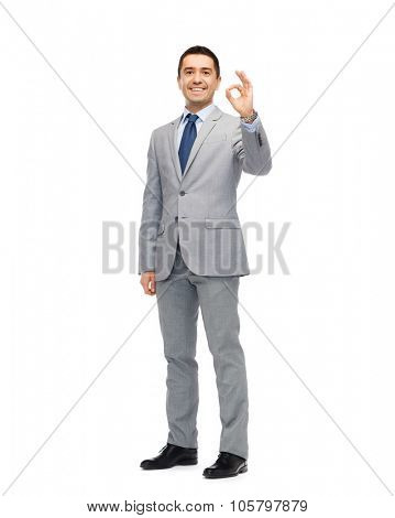 business, people, gesture and success concept - happy smiling businessman in suit showing ok hand sign