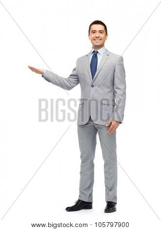 business, people, advertisement and office concept - happy smiling businessman in suit showing something imaginary