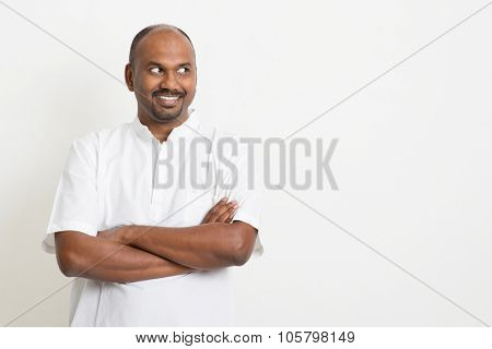 Portrait of mature casual business Indian man arms crossed looking side and smiling, copy space on side, standing on plain background with shadow.