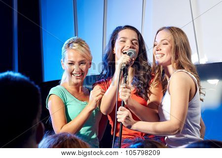 bachelorette party, karaoke, music concert and holidays concept - three happy young women or girls band singing on night club stage