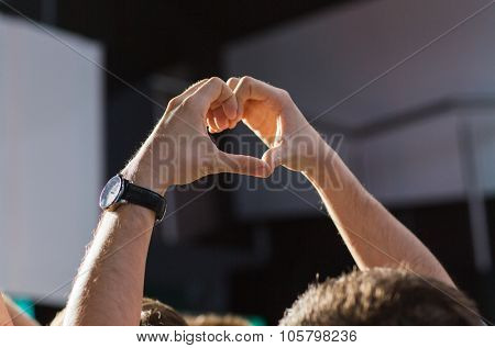 holidays, music, nightlife and people concept - close up of happy fan hands showing heart shape sign at concert in night club waving hands