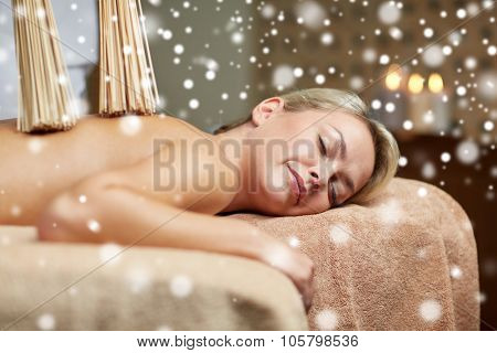 people, beauty, spa, healthy lifestyle and relaxation concept - close up of beautiful young woman lying with and having samurai back massage with bamboo brooms in spa with snow effect
