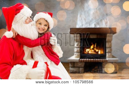 holidays, christmas, winter and people concept - happy girl with santa claus and gift box over home fireplace and lights background