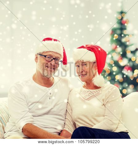 family, holidays, christmas, age and people concept - happy senior couple in santa helper hats sitting on sofa at home