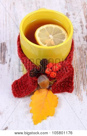 Cup Of Hot Tea With Lemon Wrapped Woolen Scarf And Autumnal Leaf, Warming Beverage For Flu