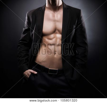 Strong, fit and sporty stripper man over black background.
