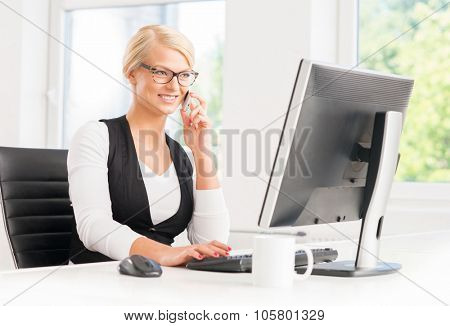 Beautiful businesswoman being busy in the office while talking by the smartphone and drinking coffee.