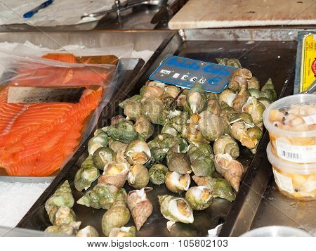 Big snails escargots stuffed with green sauce from a seafood market in Paris France.