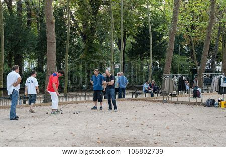 PARIS, FRANCE - SEPTEMBER 8, 2014: Playing petanque in the late afternoon in Luxemburg Garden in Paris France