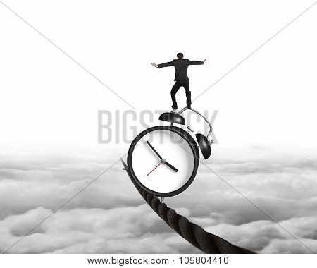 Businessman Balancing Alarm Clock On Tightrope