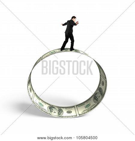 Businessman Balancing On Roll Of Dollar Bills