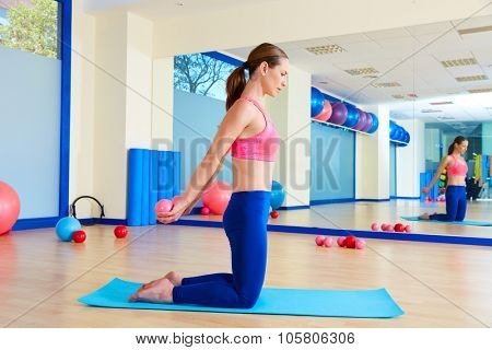 Pilates woman sand balls chest expansion exercise workout at gym indoor