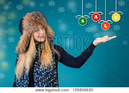 Winter Sales Concept. Winter Woman Is Pointing Showing A Word Sale On Colorful Christmas Baubles.
