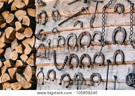 Wooden Wall With Old Rusty Horseshoes  And Firewood