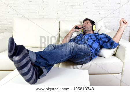 Man Falling Asleep On Home Couch While Listening To Music With Mobile Phone And Headphones