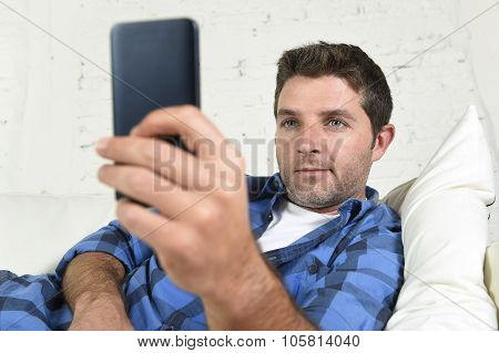 Young Attractive Man Lying Relaxed At Home Couch Texting And Surfing On Internet In His Mobile Phone