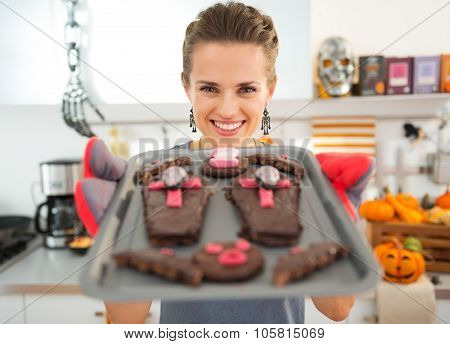 Smiling Housewife Showing Off Freshly Baked Halloween Biscuits