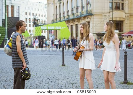 A Homeless Man Watches As Two Girls-twins Sing And Play Guitar