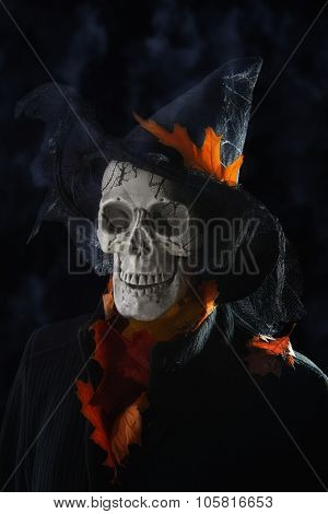 Halloween skull in witches hat with fall leaves