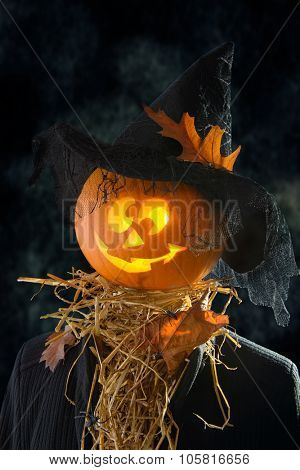 Pumpkin head wearing a witches hat with straw and spiders for Halloween