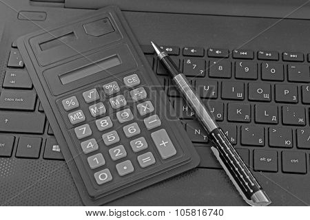 calculator and a black notebook keyboard