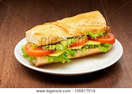Tomato cheese and salad sandwich from fresh baguette on white ceramic plate on dark wooden table