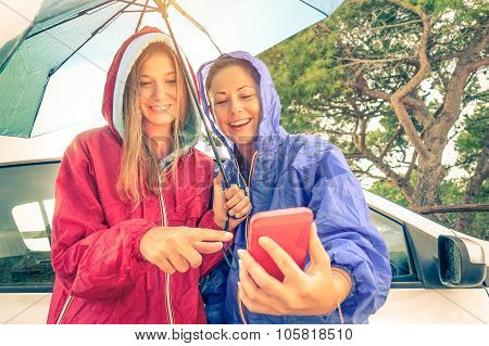 Women Best Friends Enjoying With Smartphone With Sun Coming Out After The Rain at Car Trip