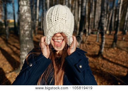 Excited Happy Fall Woman Smiling Joyful And Blissful Pull Knitted Hat Outside In Colorful Fall Fores