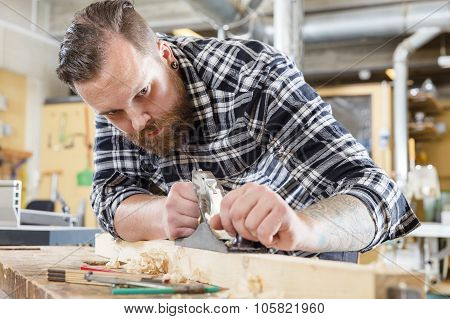 Focused carpenter work with plane on wood plank in workshop