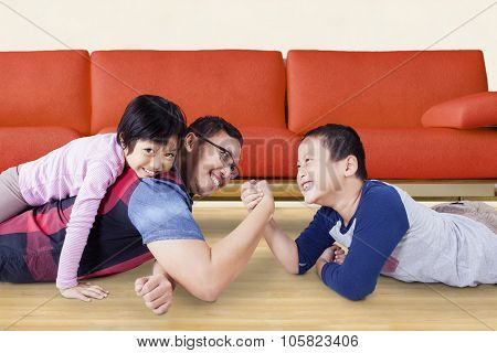 Portrait of little boy with funny expression while arm wrestling with his father at home