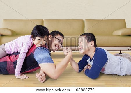 Image of young father playing with his kids and arm wrestling with his son at home
