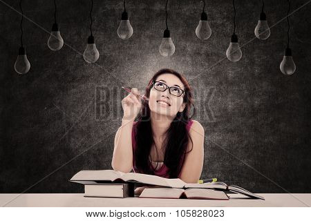 Female Student Looking At Light Bulbs