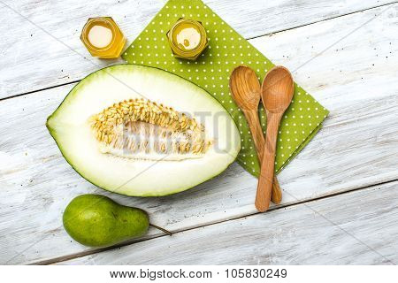 Cut Melon Honey And Green Pear On Wood