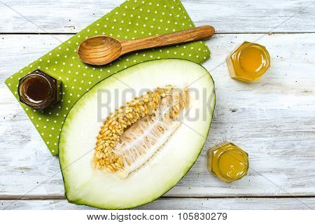 Cut Melon With Honey On Napkin And Rustic Board
