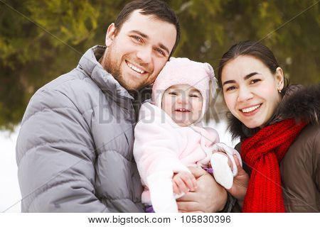 Happy Family Wearing Warm Clothes In Winter Park