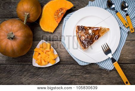 Piece Of Pie And Pumpkin Slices On Wooden Table